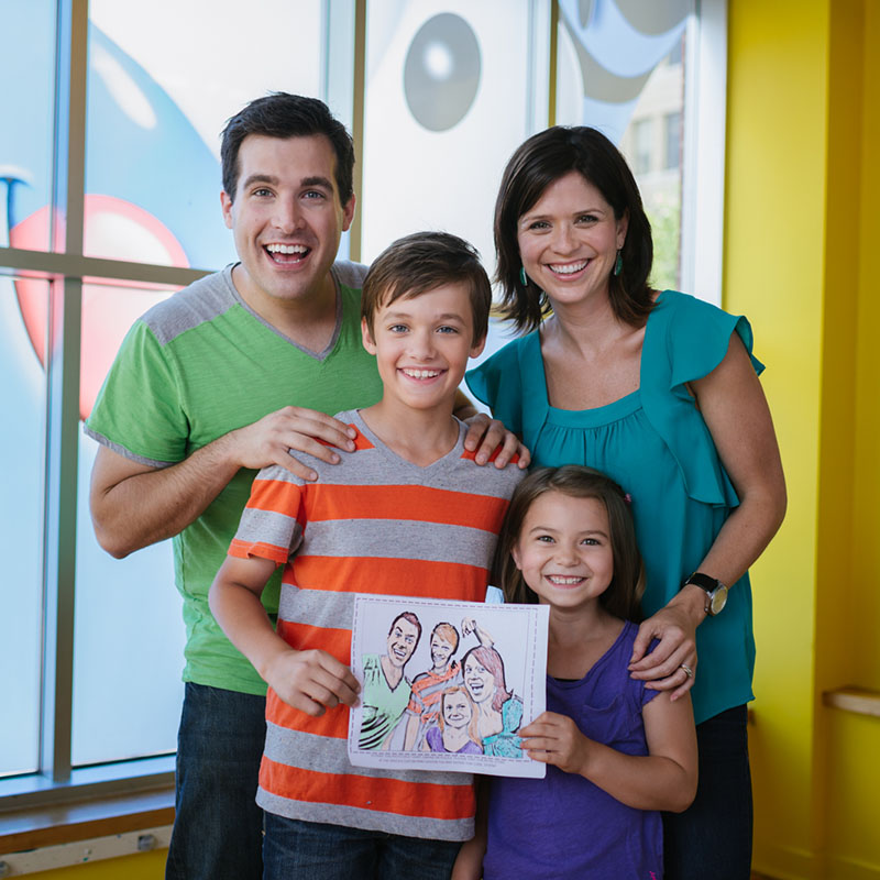 Family holding crayon drawing at Crayola Experience