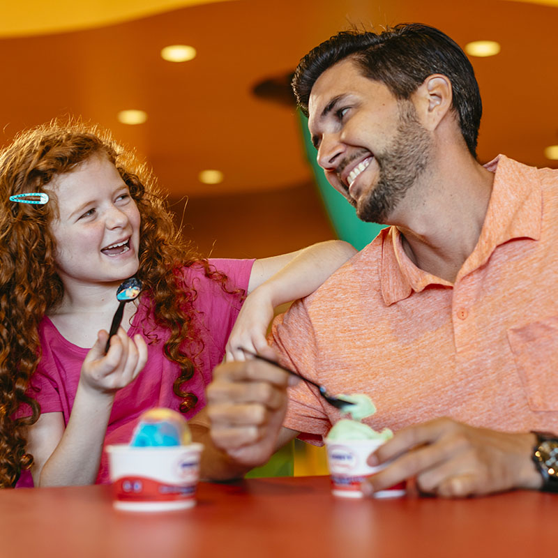 Young girl and man eating ice cream