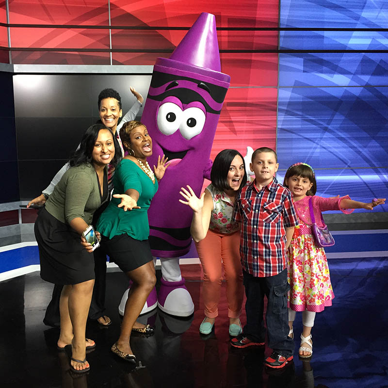 Kids and adults posing with a giant costumed crayon character