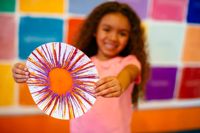 Young girl holding Spin Art at Crayola Experience
