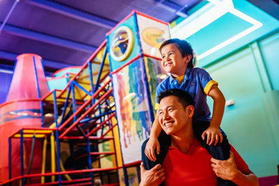 Young boy and father at the playground at Crayola Experience