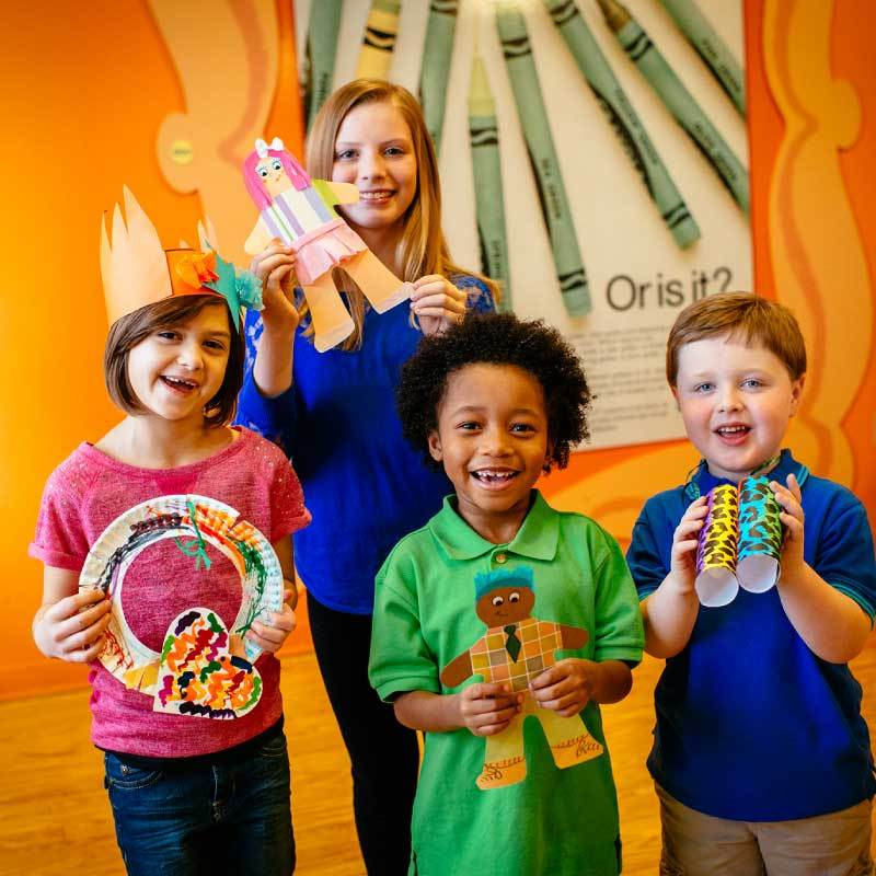 Kids with various finished Crayola Experience crafts
