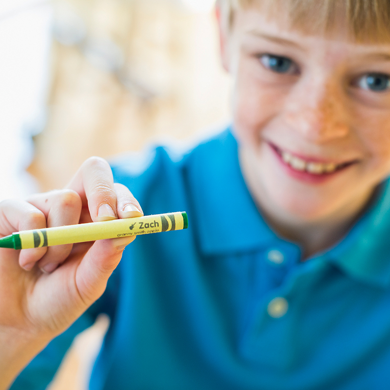 Young boy holding a green crayon