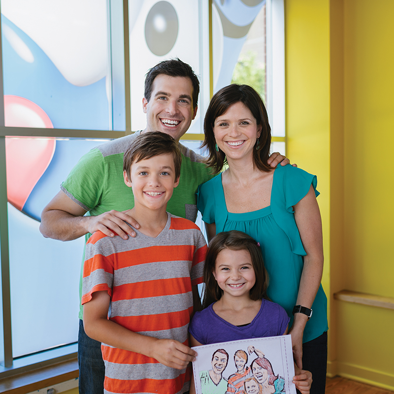 Family holding art at Crayola Experience